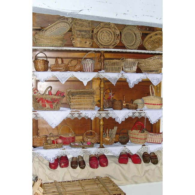Antique haberdashery postcard wooden shelf with small wicker baskets and red wooden clogs